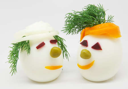 Two white eggs decorated with dill, onion and carrots on white background Stock Photo