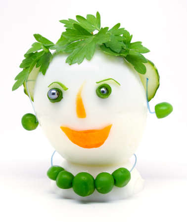 Egg garnished with parsley, cucumber, carrots and green peas on white background.