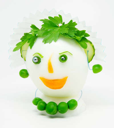 Egg garnished with parsley, cucumber, carrots and green peas on white background
