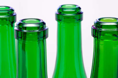 Green bottles necks close-up over white background