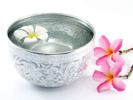 silver backgrounds: silver water bowl and Flowers, Containers for scoop water that used in the past. Currently used as decorative Asian style or in religious ceremonies