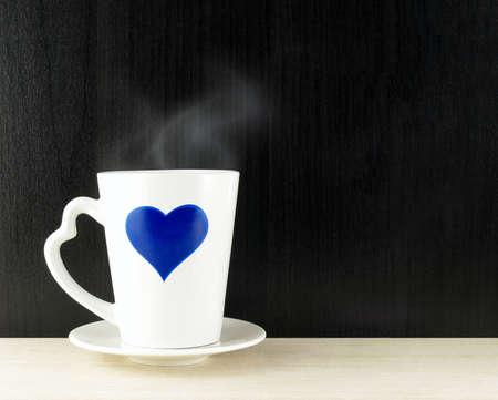 heart break: blue heart on coffee cup on wooden table background, romantic coffee break Stock Photo