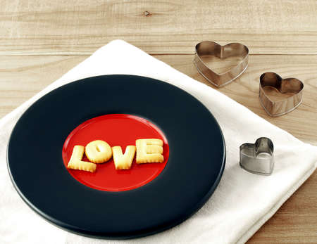 cookie cutter: love word, biscuit cookies letters on painted pottery saucer with heart shaped cookie cutter on wooden table
