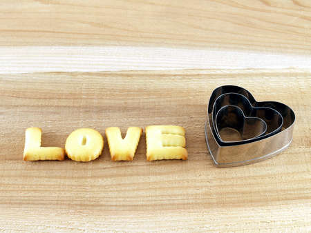 pastry cutter: love word, biscuit cookies letters with heart shaped cookie cutter on wooden background