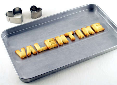 oven tray: valentine word, biscuit cookies letters on oven tray with heart shaped cookie cutter on white background Stock Photo