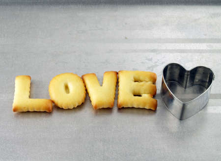 oven tray: love word, biscuit cookies letters with heart shaped cookie cutter on oven tray Stock Photo