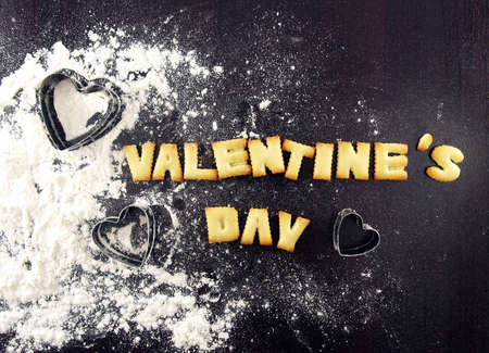 wood cutter: valentines day word, biscuit cookies letters with heart shaped cookie cutter and flour on wood kitchen table