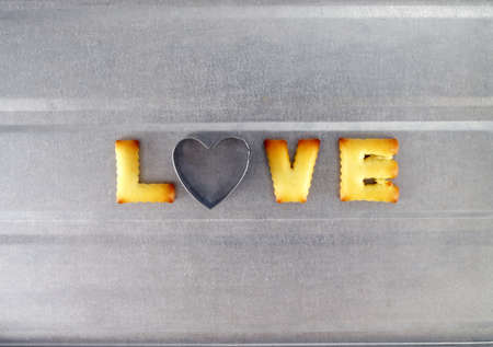cookie cutter: love word, biscuit cookies letters with heart shaped cookie cutter on oven tray Stock Photo