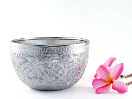 stainless steel background: silver water bowl and Flowers, Containers for scoop water that used in the past. Currently used as decorative Asian style or in religious ceremonies