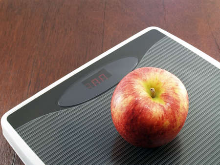 weight control: Apple on weight scale, diet concept for weight control by eating fruit