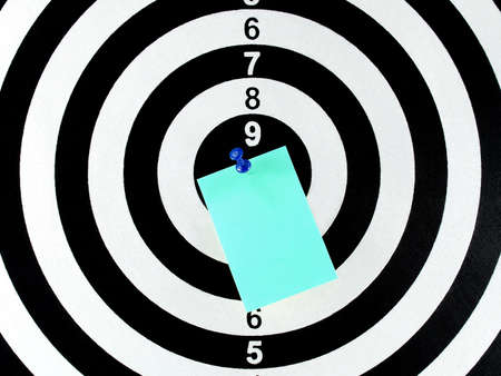 white pushpin: blank note with blue pushpin on center of dartboard, aim goal and achievement concept