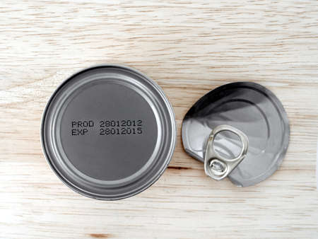 expiration date: manufacture date and expiry date printed on the bottom of aluminum cans on wooden background, Information of product for consumer, top view