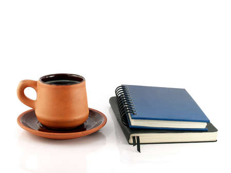 leatherette: cup of coffee with saucer and two diary books isolated on white background