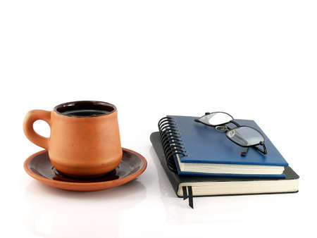 close-up brown orange pottery coffee cup with saucer and two closed diary books (blue and black) with eyeglasses isolated on white background, read and write with hot drinks in baked clay cup Stock Photo