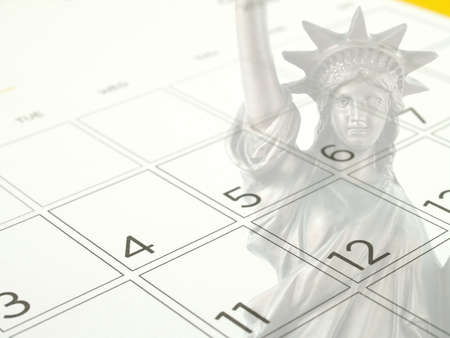 close-up desk calendar with days and dates in July 2017 and Statue of Liberty, selective focus