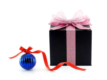 close up black cube shape cardboard gift box with pastel pink ribbon net bow and dark blue glossy christmas ball with red ribbon tied bow isolated on white background