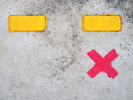 red paint cross marks on cement floor of train station platform with yellow dividing line, symbol for passengers stand to wait for train and keep distance, social distancing concept, close up top view