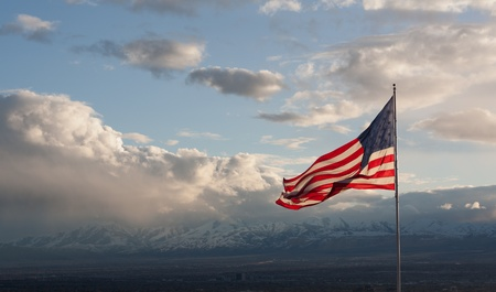 American flag with clouds and mountains