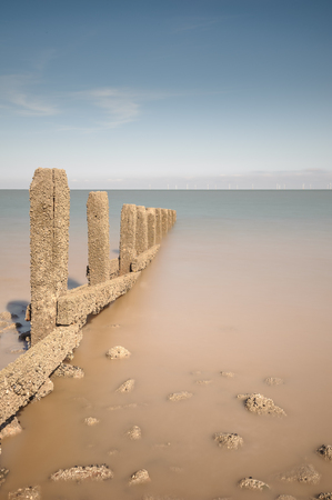 ebb: Traditional wooden groynes reach out into the sea off Llanddulas beach in North Wales. The North Hoyle offshore wind farm is on the horizon. Stock Photo
