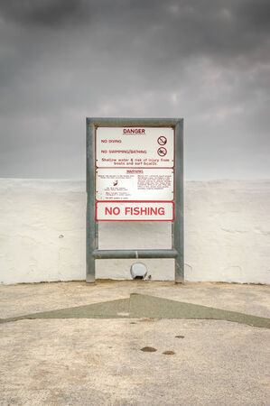 No Swimming, No Fishing warning sign indicating danger from boat collision and Weaver Fish stings, which usually require Hospital treatment. photo