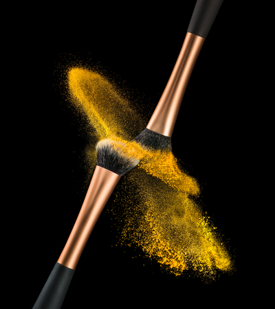 A high speed action capture of powder exploding off two makeup brushes as they are rubbed together.