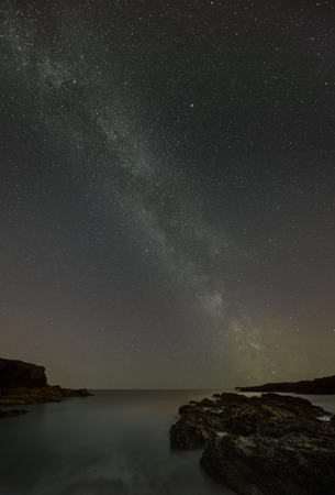 galactic center: The Milky Way over the coastline of Anglesey in North Wales, showing light pollution and the phenomenon of air glow. Stock Photo