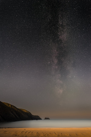 galactic center: The Milky Way over a small moonlit bay on the coast of North Wales. Stock Photo