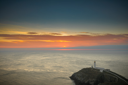 South Stack Lighthouse on the island of Anglesey in North Wales. The sun has set behind rain clouds and haze over the Irish Sea.