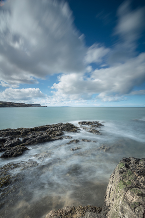 A North Wales seascape featuring the incoming tide swirling around rocks on a fine sunny day at Penmon Point on the island of Anglesey in North Wales. Standard-Bild
