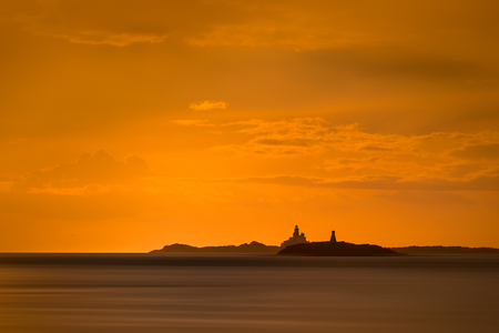 The Skerries Lighthouse and West Mouse, two famous landmarks on the North Wales coast, against the orange sky of an approaching sunset. Standard-Bild