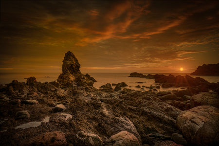 The rock stack lying off the boulder-strewn beach of Porth Saint, Rhoscolyn Head, Anglesey.