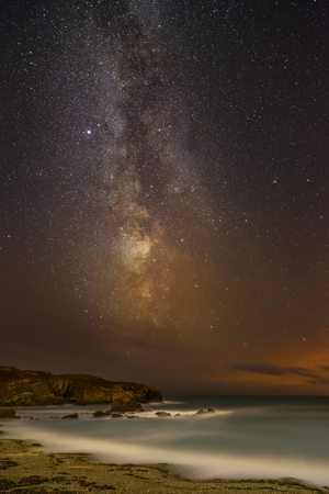 The Milky Way becomes visible through a gap in the clouds on a stormy night over Porth Y Post on the Anglesey coast in North Wales.