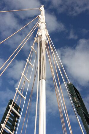 Broome pearl lugger boat from the side  Contrasting masts against bright blue sky with white scattered clouds photo