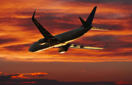 undercarriage: Airplane taking off infront of a beautiful sunset Stock Photo