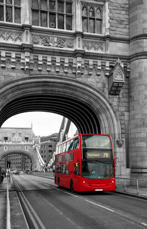 Red London bus passing over Tower Bridge in black and white with selective colour.