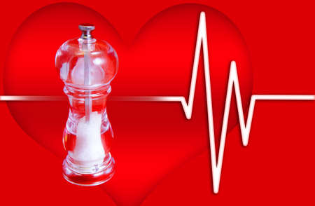 Salt Mill on Heart Background - Excess salt causes high blood pressure photo