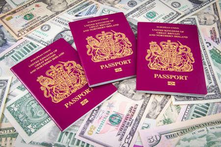pasaporte: Reino Unido Pasaporte en una pila de dólares