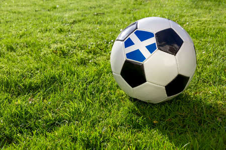Football on a grass pitch with Scotland Flag
