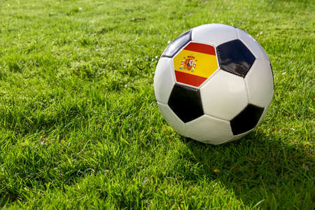 Football on a grass pitch with Spain Flag
