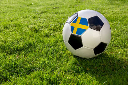 Football on a grass pitch with Sweden Flag