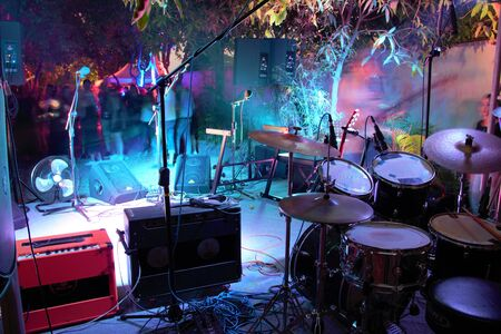 Drum set and guitar amps looking out on stage and into the audience at a small gig