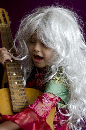 plays: Girl wig sings and plays guitar in the gypsy dress