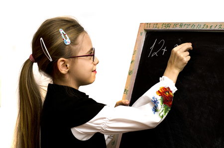 young schoolgirl: schoolgirl wrote on the blackboard isolated on a white background