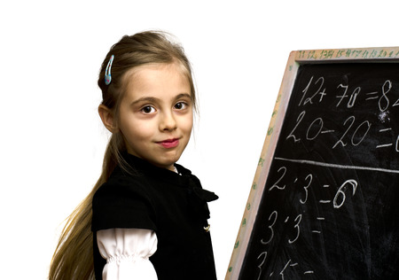 smiling schoolgirl standing near the blackboard isilated on a white background