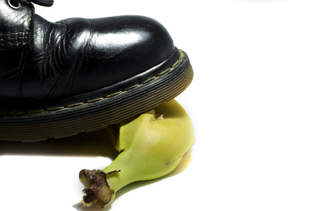 bad banana: old shoe slips on a banana peel isolated on a white background