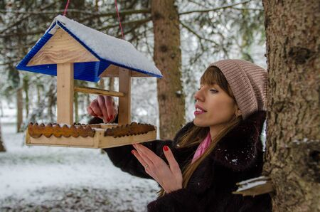 the girl pours the feed into the feeder in the winter frosty park