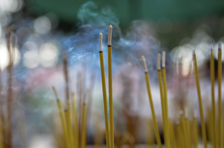 Burning yellow incense sticks in a pot. Aromatic sticks and smoke in a Buddhist temple in Cambodia