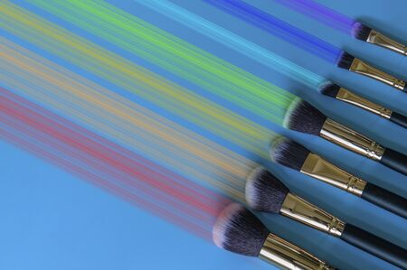 Professional makeup brushes on eyeshadow with a trace of rainbow on blue background