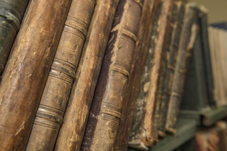 Vintage, antiquarian books pile on wooden surface in warm directional light. Selective focus. Stock Photo