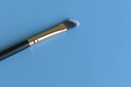 Professional makeup brush on blue background 스톡 콘텐츠